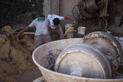 Obreros de la construcción preparan la mezcla con arena y cemento.