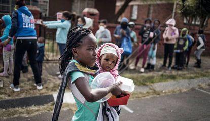 Una niña con un bebé en brazos recoge la comida que una asociación reparte en Johannesburgo (Sudáfrica) para las familias más pobres.