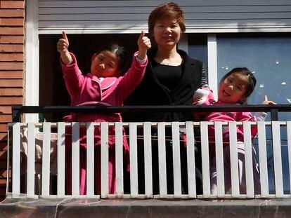 Wei Chen y sus hijas saludan desde el balcón de su piso de Barcelona, donde llevan una semana confinadas.