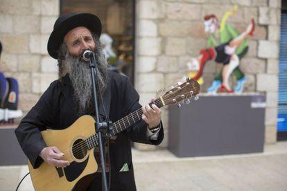 Un judío ultraortodoxo toca la guitarra en un centro comercial israelí.