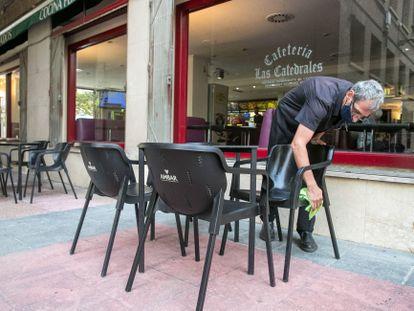 Un hostelero desinfecta el mobiliario de la terraza de su establecimiento en la Plaza del Pilar de Zaragoza, este martes.