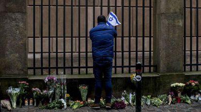 Un hombre pone una bandera israelí en la sinagoga de Copenhague.