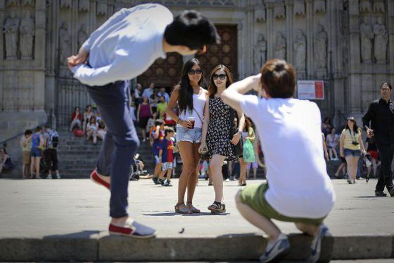 Dos turistas posan en la plaza de la Catedral de Barcelona.