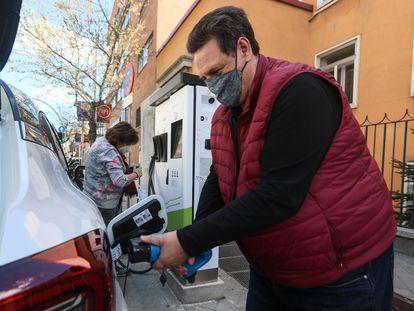 Varios usuarios recargan su vehículo en un punto de recarga de coches eléctricos en Madrid.
