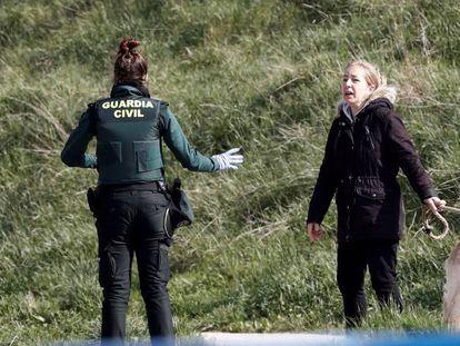 Una guardia civil advierte a una mujer de que se ha alejado demasiado de su vivienda.
