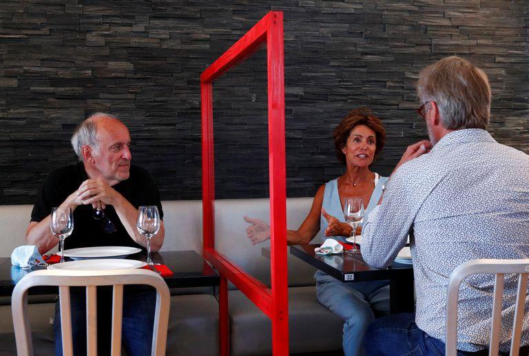 Un restaurante de Bruselas prueba una barrera de plexiglás entre las mesas.