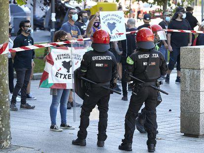 Agentes de la Ertzaintza contienen a los manifestantes que se concentran contra la participación del secretario general y diputado de Vox, Javier Ortega Smith,en Santurtzi.