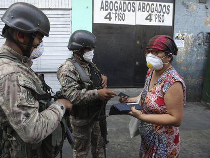 Dos soldados detienen a una mujer en un retén en Lima durante el estado de emergencia decretado en el país.