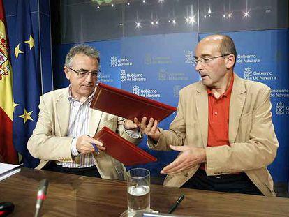 Miguel Sanz (a la izquierda) intercambia con Juan Cruz Alli (CDN) los documentos del acuerdo de gobierno.