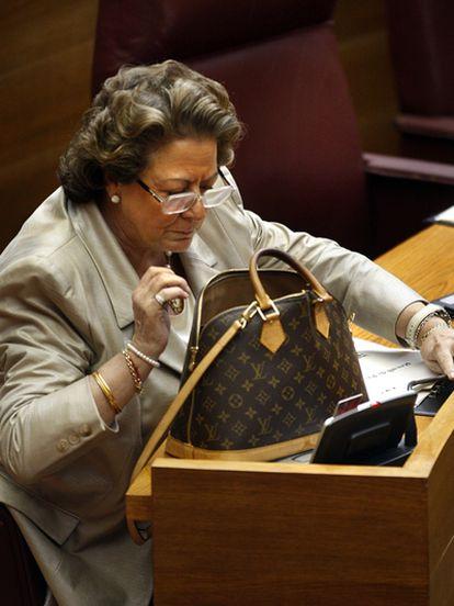 Rita Barberá busca algo en su bolso que lleva estampada la marca Louis Vuitton en un pleno de las Cortes