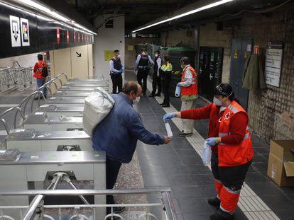 Voluntarios de Cruz Roja reparten mascarillas en el metro de Sants de Barcelona.