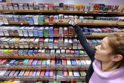 Una estanquera muestra cajetillas de tabaco de distintas marcas.