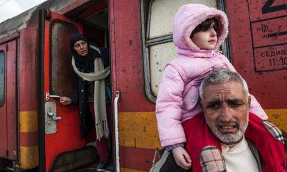 Tres migrantes esperan este miércoles en un tren para cruzar la frontera entre Grecia y Macedonia.