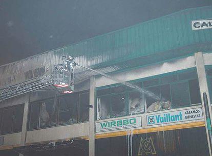 Un bombero apaga una de las naves que resultó afectada por el incendio.