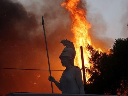 Una estatua de Palas Atenea, diosa griega de la guerra, rodeada por el fuego en el suburbio ateniense de Varympompi la noche del martes.
