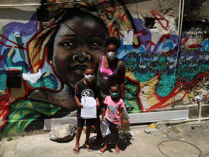 Janice Delfim, fundadora de una iniciativa para facilitar el acceso a la educación de los niños perjudicados por el cierre de escuelas por la covid-19, posa con dos de las beneficiarias de su proyecto, en la favela Prazeres de Río de Janeiro, en Brasil.