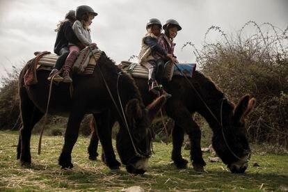 Dos pares de niños encima de sendos burros, durante una salida en invierno.