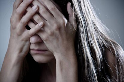 Una mujer cubre su rostro.