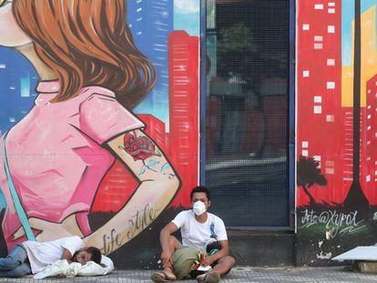 Dos sin techo descansan frente a un mural, en Sao Paulo.