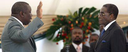 Morgan Tsvangirai, a la izquierda, levanta su mano para jurar como primer ministro ante Robert Mugabe.