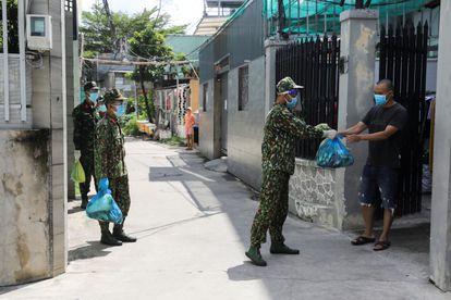 Soldados vietnamitas reparten comida a vecinos de Ciudad Ho Chi Minh, en Vietnam, este martes.