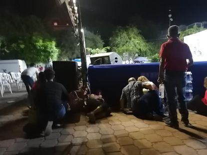Los asistentes al Festival Cultural Yohuala 2021 en Iguala, Guerrero, se resguardan durante el tiroteo del domingo.