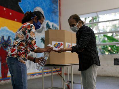 Una mujer ofrece gel antibacterial en un colegio electoral de Caracas, este domingo durante la celebración de elecciones legislativas.