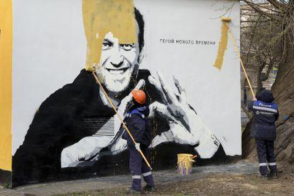 Empleados municipales pintan sobre un mural con el retrato de Navalni, el pasado abril en San Petersburgo.