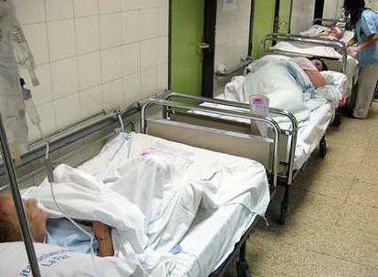 Varios pacientes esperan en los pasillos de Urgencias de La Paz a que les lleven a una habitación. Al fondo, una enfermera les atiende.