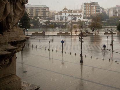 Un solitario ciclista pasea bajo la lluvia frente al palacio de San Telmo en Sevilla.