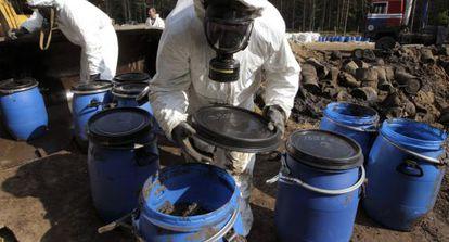 Operarios manejan bidones con contaminantes tóxicos.