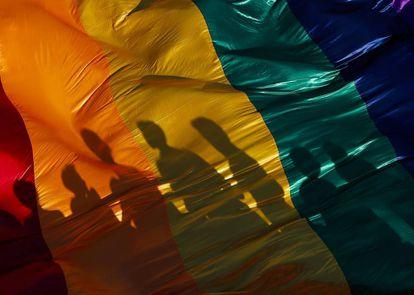 La sombra de unos participantes en una marcha del Orgullo LGTBQ en Managua se refleja sobre la bandera del arco iris, símbolo de la causa.