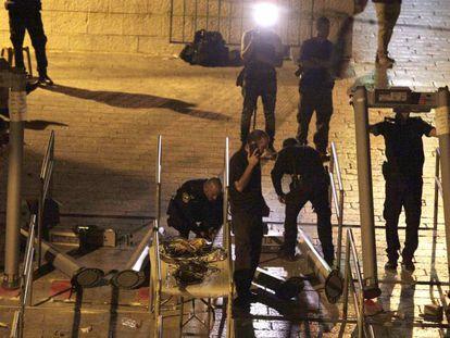Varios personas retiran detectores de metales en la entrada de la Explanada de las Mezquitas.