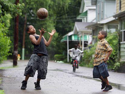 Dos niños juegan a baloncesto en una calle de Akron, estado de Ohio.
