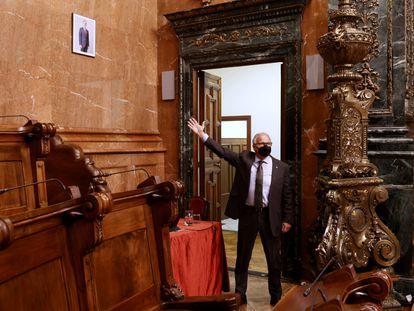 El concejal por el PP Josep Bou señala el minúsculo retrato del Rey.