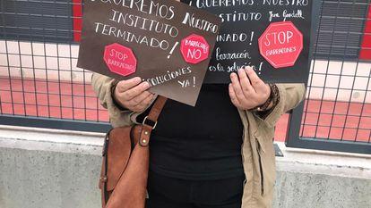 Una madre muestra dos carteles durante una protesta rente al instituto de Rejas.