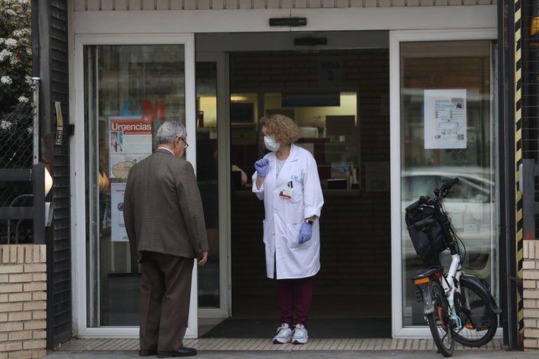 Una sanitaria espera este sábado a los pacientes a la puerta de un centro de salud en Madrid.