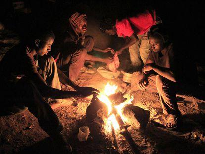 Un grupo de africanos preparan su cena en el monte Gurugú, en Marruecos, cerca de Melilla