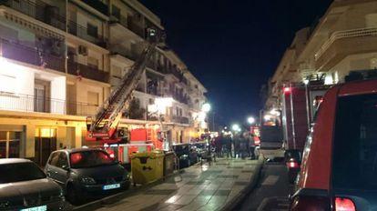 Los bomberos tratan de rescatar a los vecinos de la vivienda incendiada en Rafelbunyol en diciembre de 2014.