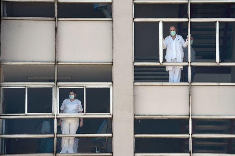 Médicos miran a través de las ventanas del Hospital Universitario de A Coruña.