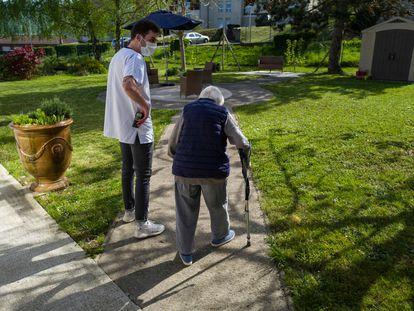 Un trabajador de una residencia en Thises, en el este de Francia, acompaña a una anciana en su paseo por el jardín del centro