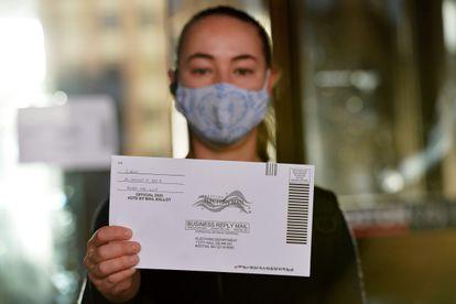 Una mujer sostiene una papeleta para votar por correo en las primarias de Massachusetts, el 1 de septiembre de 2020.