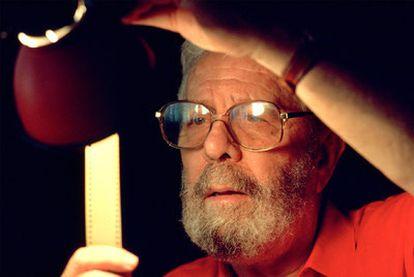 El cineasta revisando unos negativos en una imagen de 1990