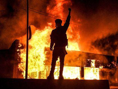 Un manifestante alza un brazo frente a un edificio en llamas incendiado durante una manifestación en Minneapolis.