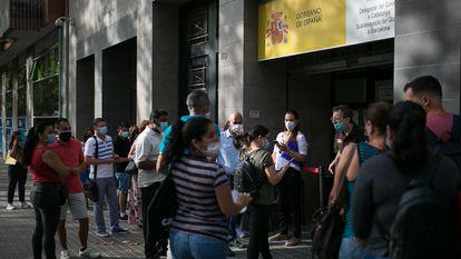 Cola de personas en las puertas de la oficina de Extranjería, en Barcelona.