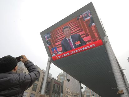 Un hombre fotografía una pantalla que muestra un discurso de Xi Jinping en Pekín.