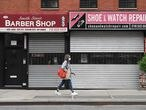 (FILES) In this file photo taken on May 5, 2020, a woman walks by a closed barber shop and shoe and watch repair store in the Brooklyn borough of New York City. - Lockdown measures in New York City have been extended until June 13 under an executive order signed by state Governor Andrew Cuomo late May 14, 2020. Stay at home orders will be eased for the state's five least populated regions, however, allowing businesses there to get back to work gradually. (Photo by Angela Weiss / AFP)
