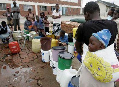 Un grupo de personas espera para recibir agua potable en Harare.