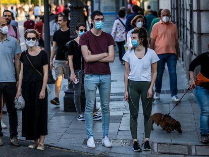 Varias personas esperan en un semáforo en la calle Bailen de Madrid.