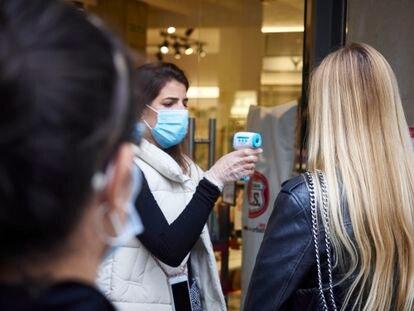 Una empleada de una tienda de moda en Pamplona toma la temperatura a una clienta a la entrada.